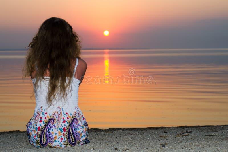 海的女孩日落的 免版税库存照片