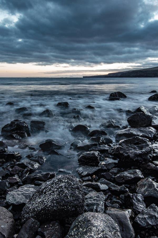 海的岩石海岸美丽的射击有令人惊讶的水纹理和惊人的多云灰色天空的 库存图片