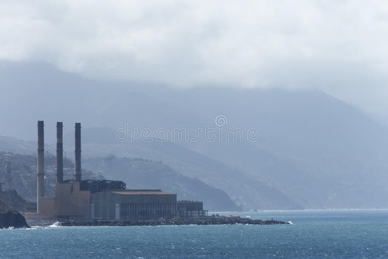 海的工厂,在山前面 库存图片