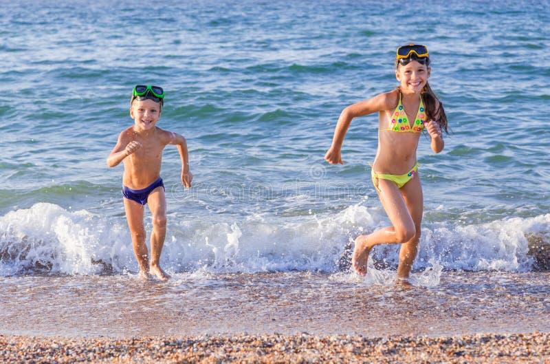 从海的愉快的孩子奔跑 免版税库存照片