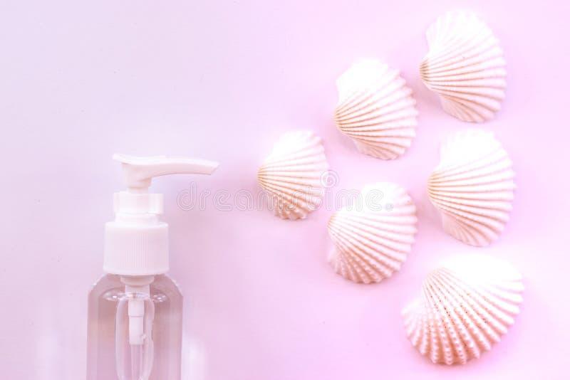 海的气味 有壳的塑料香水喷子瓶在粉红彩笔背景 免版税库存照片