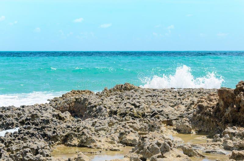 海的波浪刺穿的岩石 在与海的波浪的冲击造成的岩石的孔 免版税库存照片
