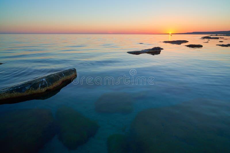 海的海岸有石头的在日落 库存照片
