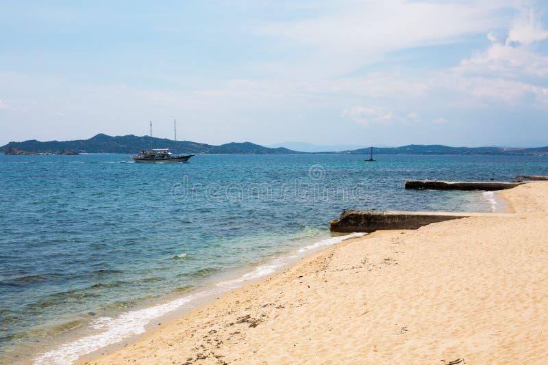 海的看法,海岸,有到达对Ouranoupoli村庄,希腊口岸的游人的船  免版税库存照片
