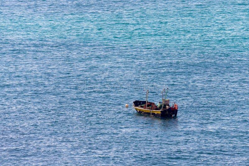 海的Minimalistic图象有渔船的 蓝色海水和清楚的天空 库存照片