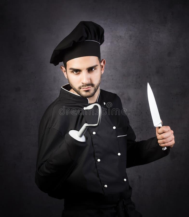 海盗式厨师烹饪器材的一张幽默画象在黑色的 免版税库存照片