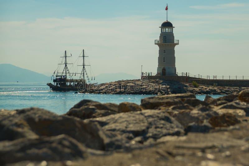 海盗式船和一座灯塔在离阿拉尼亚的附近海岸  海和山在天际 阿拉尼亚,安塔利亚区,土耳其, 免版税库存图片