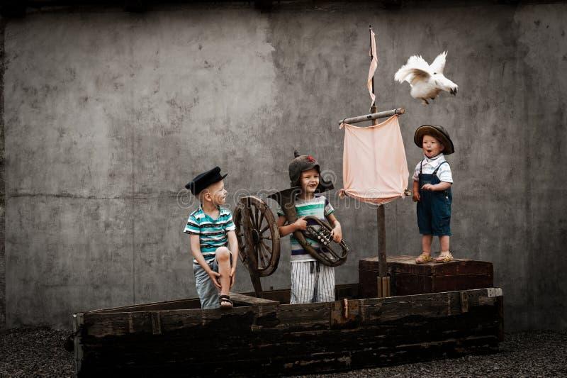 海盗船的三个逗人喜爱的男孩作为水手 免版税库存照片