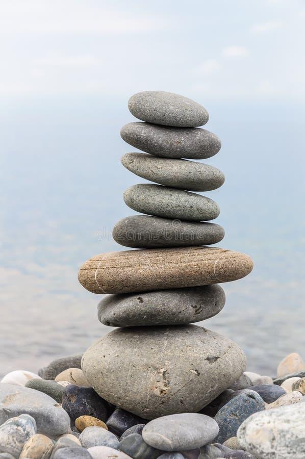 海石头金字塔在海岸的小卵石的 海景 平衡和灵性的概念 免版税库存图片