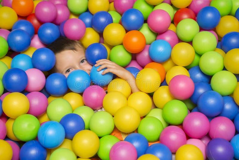 海绵看照相机的球水池的逗人喜爱的微笑的男孩 使用与在操场球水池的五颜六色的球的孩子 免版税库存图片