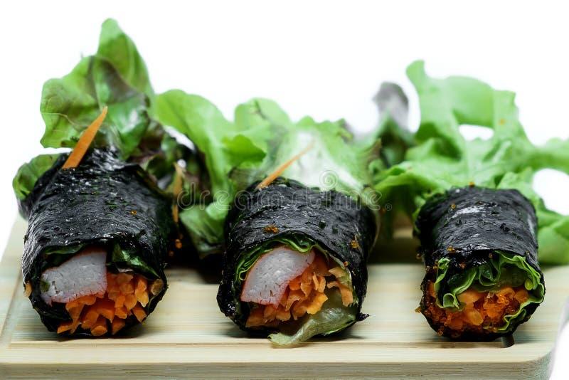 海草与新鲜蔬菜的沙拉卷和螃蟹在木板材和白色背景黏附 免版税图库摄影