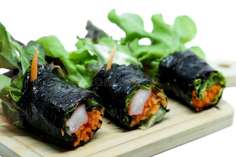 海草与新鲜蔬菜的沙拉卷和螃蟹在木板材和白色背景黏附 图库摄影