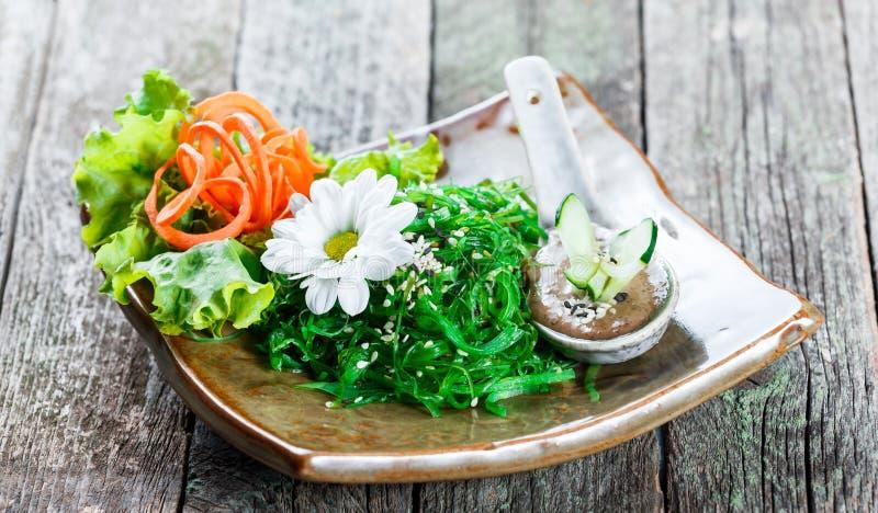 海草在板材的沙拉wakame有在竹席子的筷子的 日本烹调-健康海鲜 库存照片