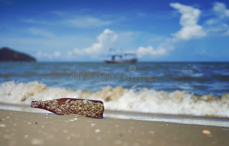 海被倾销的一个棕色玻璃瓶的橡子殖民地在背景中污染在海波浪沙子海滩、被弄脏的飞溅和蓝天 库存照片