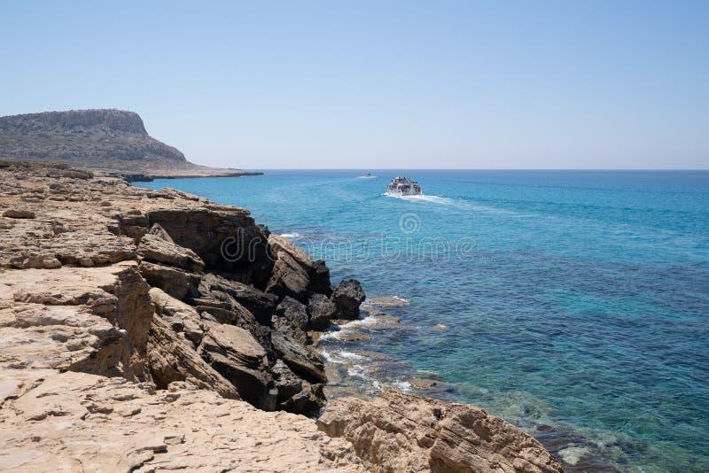 海角与通过Cavo格雷科,品柱格雷科的旅游船的格雷科风景 库存图片