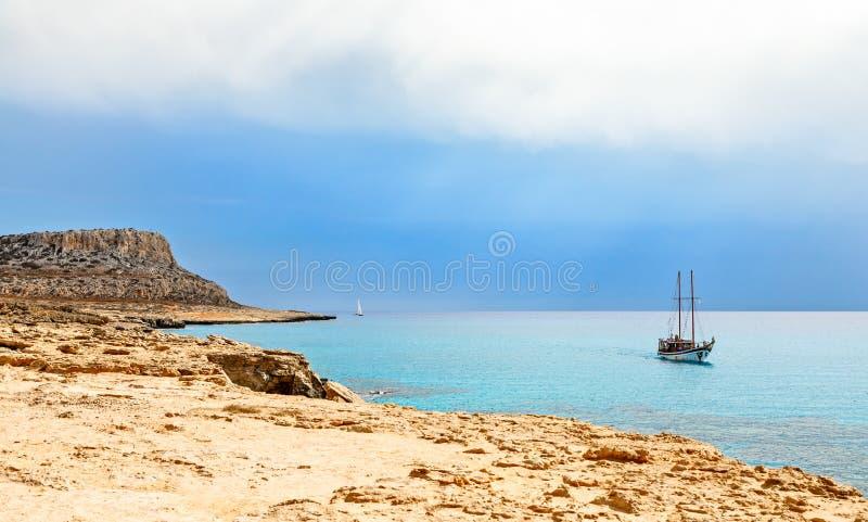 海角有蓝色海和游艇的在前景, A格雷科全景 库存照片