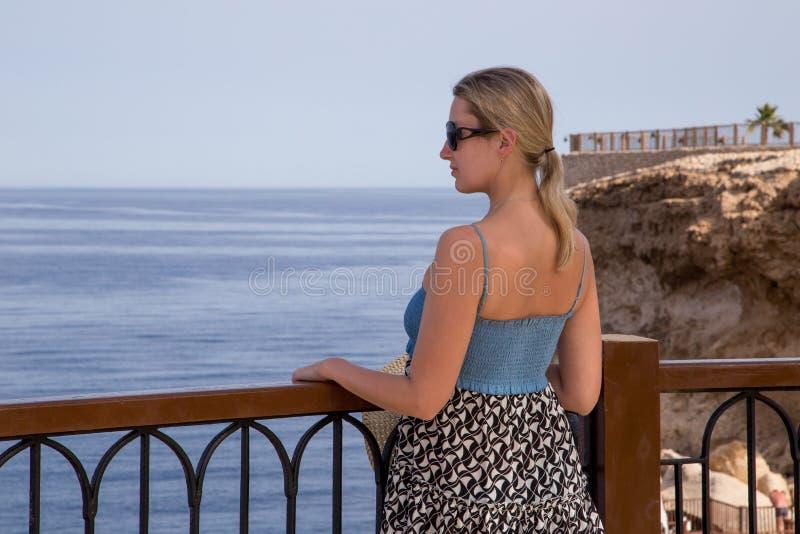 海边大阳台的女孩 库存照片