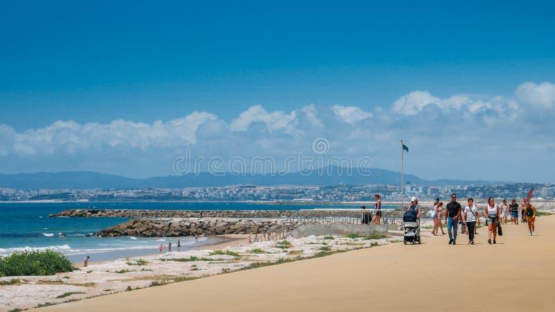 海边散步的人们在科斯塔da卡帕里卡,阿尔马达,葡萄牙 免版税库存照片