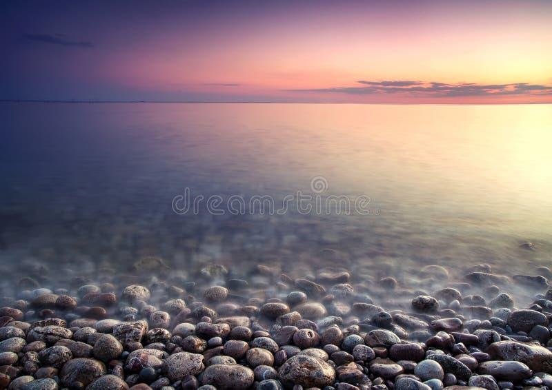 海运小卵石。 本质结构的日落。 免版税图库摄影