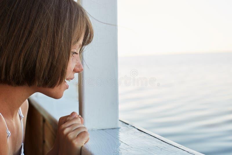 海远航概念 有有浮动的头发的小女孩在船的海旅行,看从甲板,有激动的神色的观看的海 逗人喜爱 库存图片
