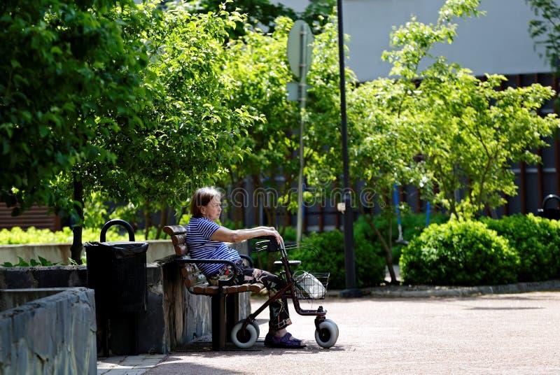 海门林纳,有她的步行者的芬兰06/08/2019年长残疾妇女在公园 免版税库存照片