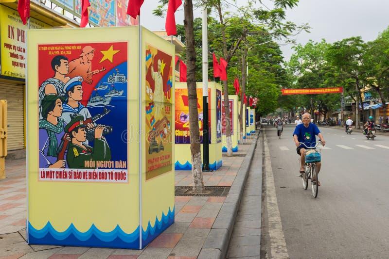 海防,越南- 2015年4月30日:一个人在通过统一天宣传的街道上循环 统一天指示事件w 库存照片