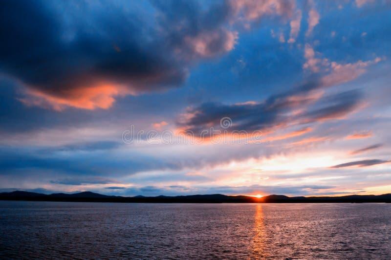海风景-日落夏天光点燃的海水 海与山脉和剧烈的云彩的夏天自然 免版税图库摄影