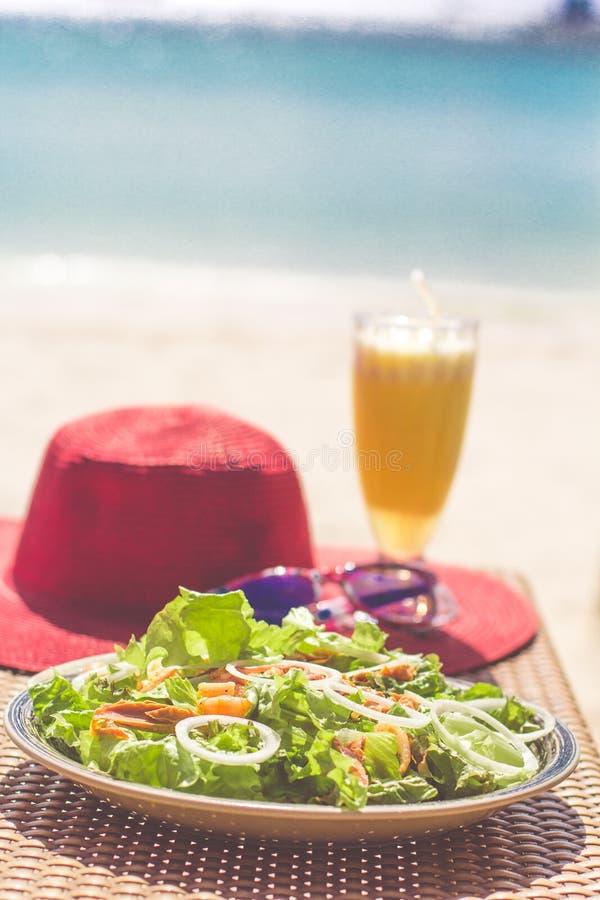 海鲜沙拉、橙色新鲜的汁液、帽子和太阳镜在桌上在海附近 免版税图库摄影