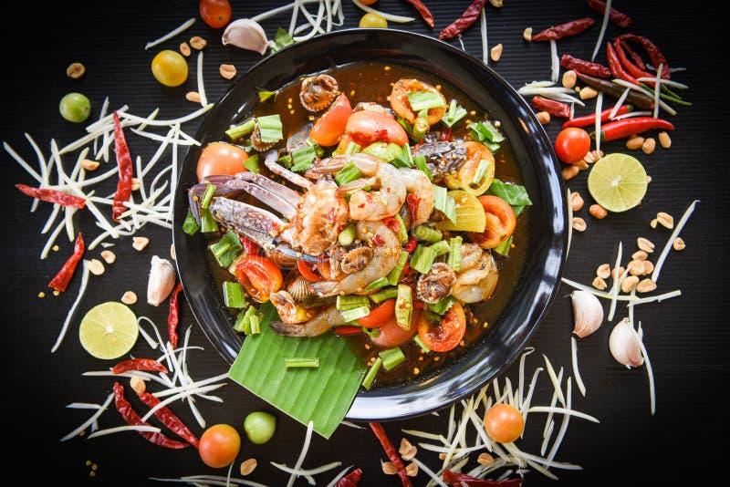 海鲜沙拉辣与在黑色的盘子新鲜蔬菜草本和香料成份服务的新鲜的虾螃蟹鸟蛤用辣椒 免版税库存图片