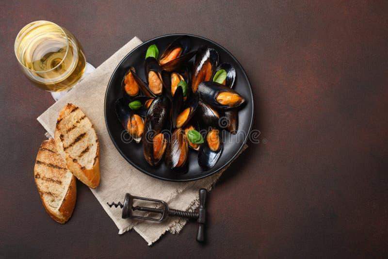海鲜淡菜和蓬蒿叶子在一个黑色的盘子有葡萄酒杯的,拔塞螺旋,面包切片,粗麻布在生锈的背景 库存照片