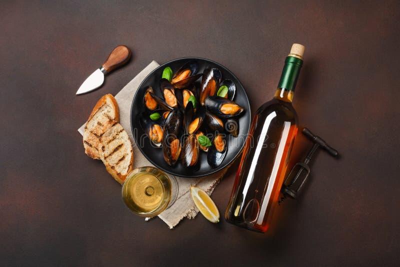 海鲜淡菜和蓬蒿叶子在一个黑色的盘子有酒瓶的,葡萄酒杯,拔塞螺旋,面包切片,粗麻布在生锈的背景 免版税图库摄影