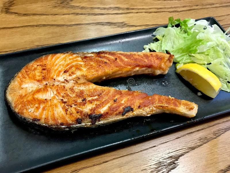 海鲜烤了三文鱼用柠檬在餐馆服务 免版税库存图片