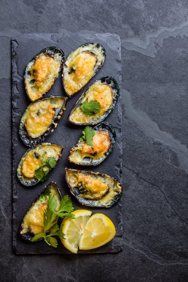 海鲜 被烘烤的淡菜用乳酪和柠檬在壳 免版税库存图片