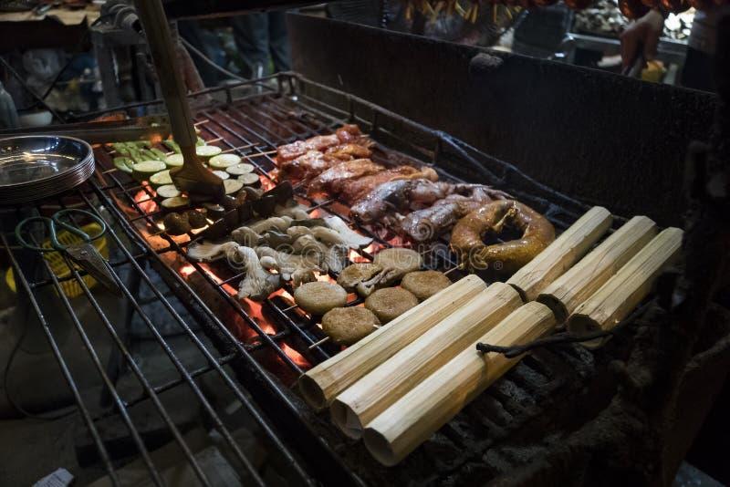 海鲜kebab,菜,肉,在竹子烘烤的米在格栅户外被烹调在街道上的晚上 库存照片
