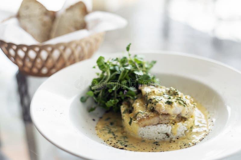 海鲷在板材的乳脂状的芥末莳萝和柠檬调味汁餐馆膳食鱼片 库存照片