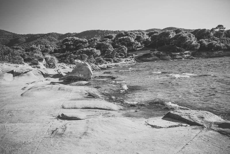 海,明白,在大石头,岩石附近的透明水多岩石的海滩  自然风景在晴朗的夏日 概念查出的本质白色 免版税库存照片