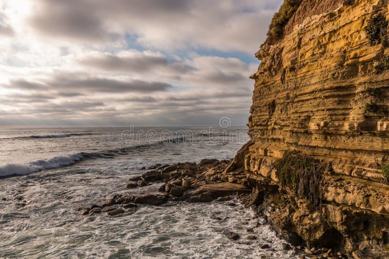 海洋、峭壁和岩石在日落峭壁在圣地亚哥 库存照片