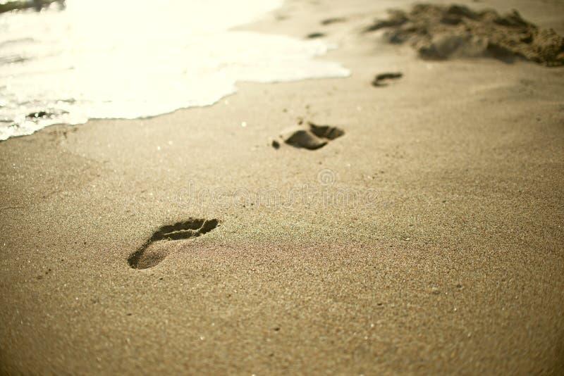 海滩、波浪和脚步 免版税库存照片