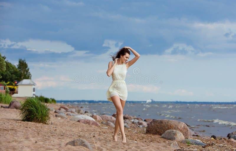 去海滩一个微笑的赤足女孩的画象 免版税库存图片