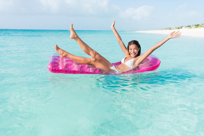 海滩乐趣女孩嬉戏在海洋浮游物床垫 库存图片