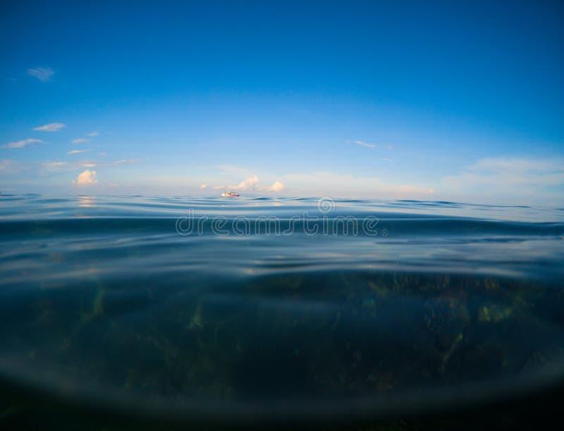 海洋和深蓝天在黄昏 与海水和天空的双重风景 免版税库存图片