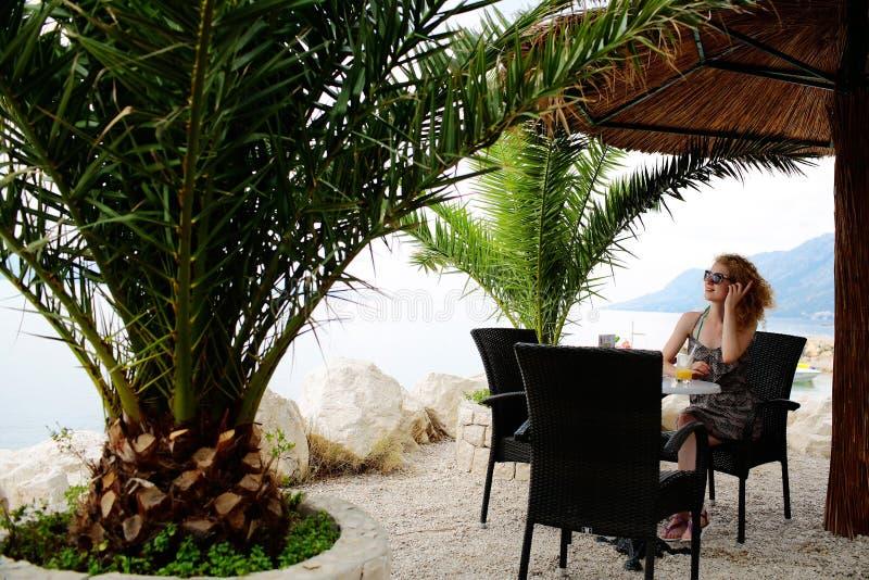 海滩咖啡馆的俏丽的女孩 免版税库存照片