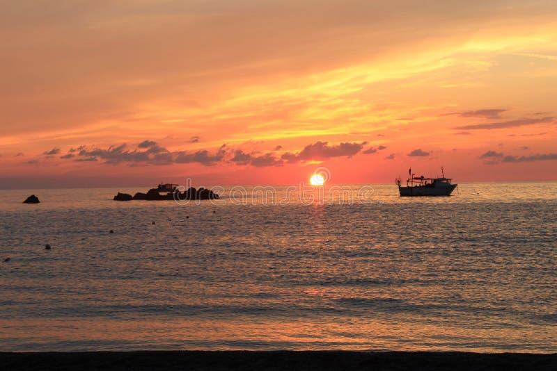 海&天空红色岩石小船 免版税图库摄影