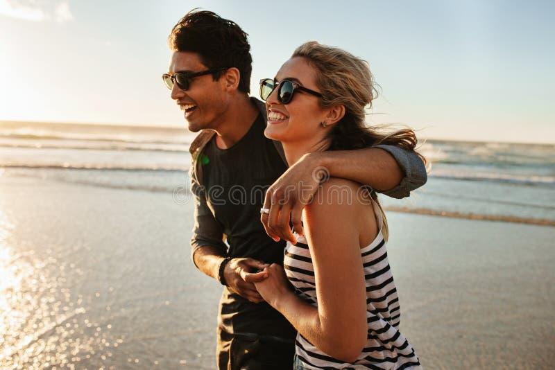 海滩夫妇微笑的走的年轻人 免版税库存图片
