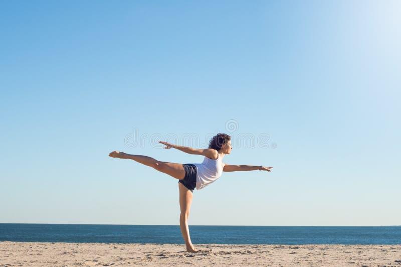 海滩实践的女子瑜伽 图库摄影