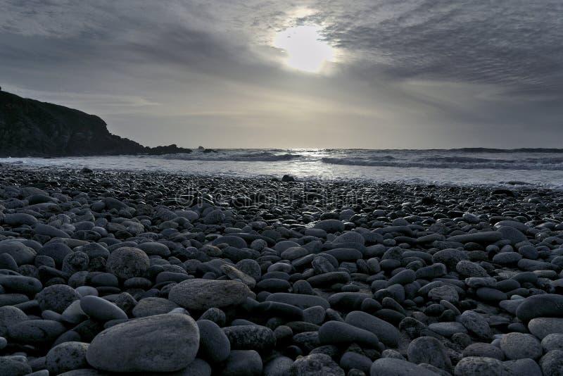 海滩小卵石海景日落 库存图片