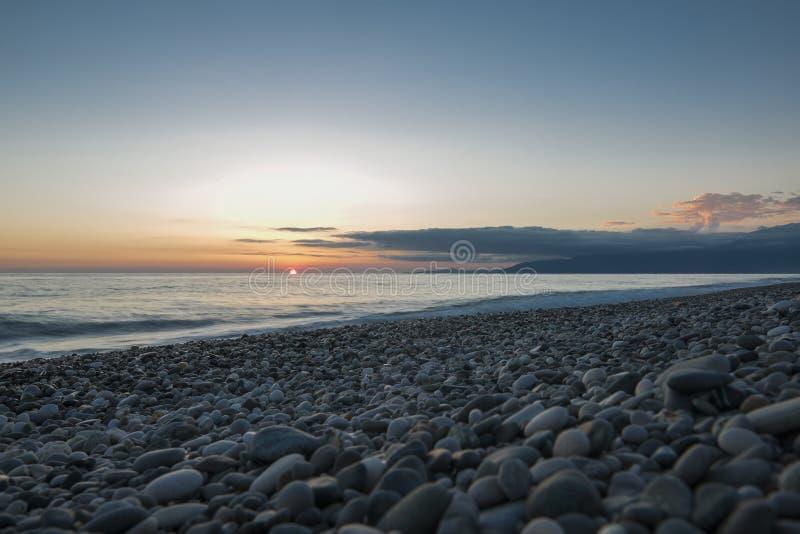 海滩小卵石海景日落 免版税库存图片