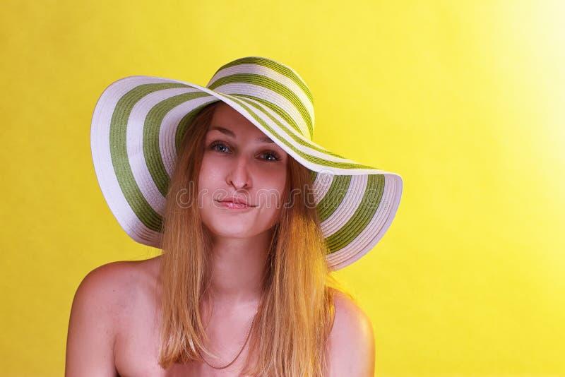 戴海滩帽子和眼镜的微笑的美丽的女孩 免版税库存图片