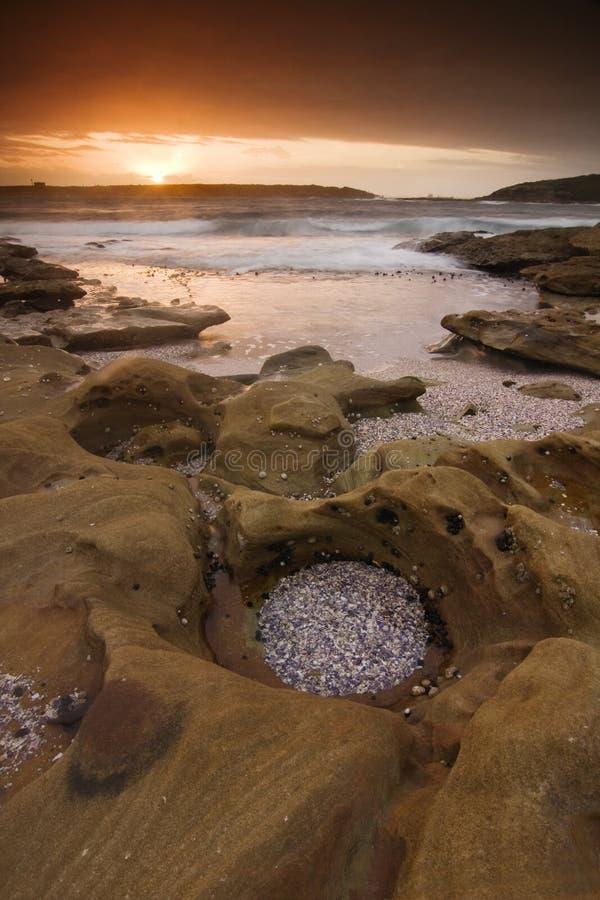 海洋日出风景有波状云和岩石的 免版税库存图片