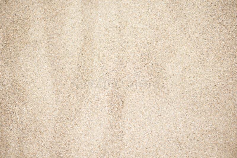 海滩沙子背景 金黄沙子美好的纹理在特写镜头拍摄了 免版税库存图片